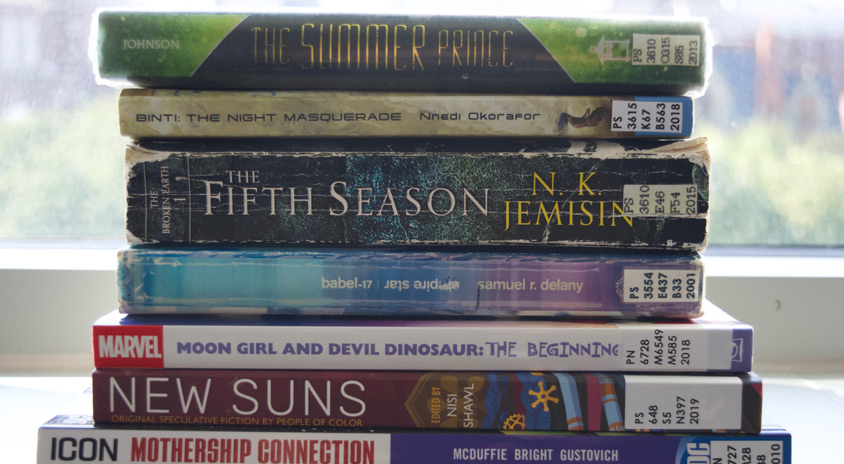 A stack of books with titles including Mothership Connection, New Suns, Moon Girl and Devil Dinosaurs, The Fifth Season, The Night Masquerade, The Summer Prince