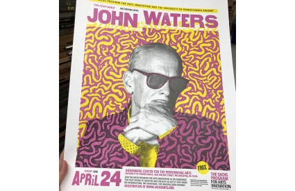 Brightly colored poster with image of John Waters at center