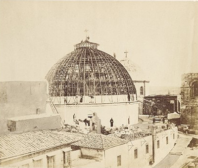Photo showing scaffolding for the dome with nearby structures in the foreground.