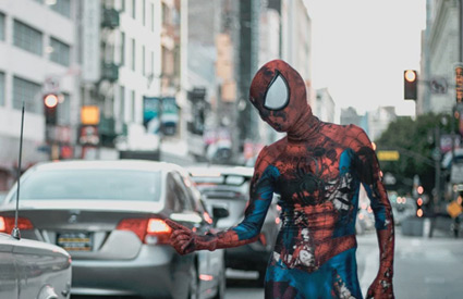 Ragged Spiderman hitchhiking in city traffic