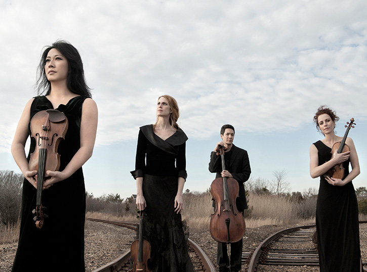 Photo of Daedalus Quartet members stand on railroad track junction. Photo Credit: Lisa-Marie Mazzucco