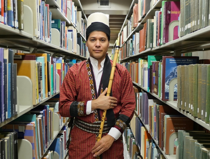 Juan Castrillón holding a ney in library stacks
