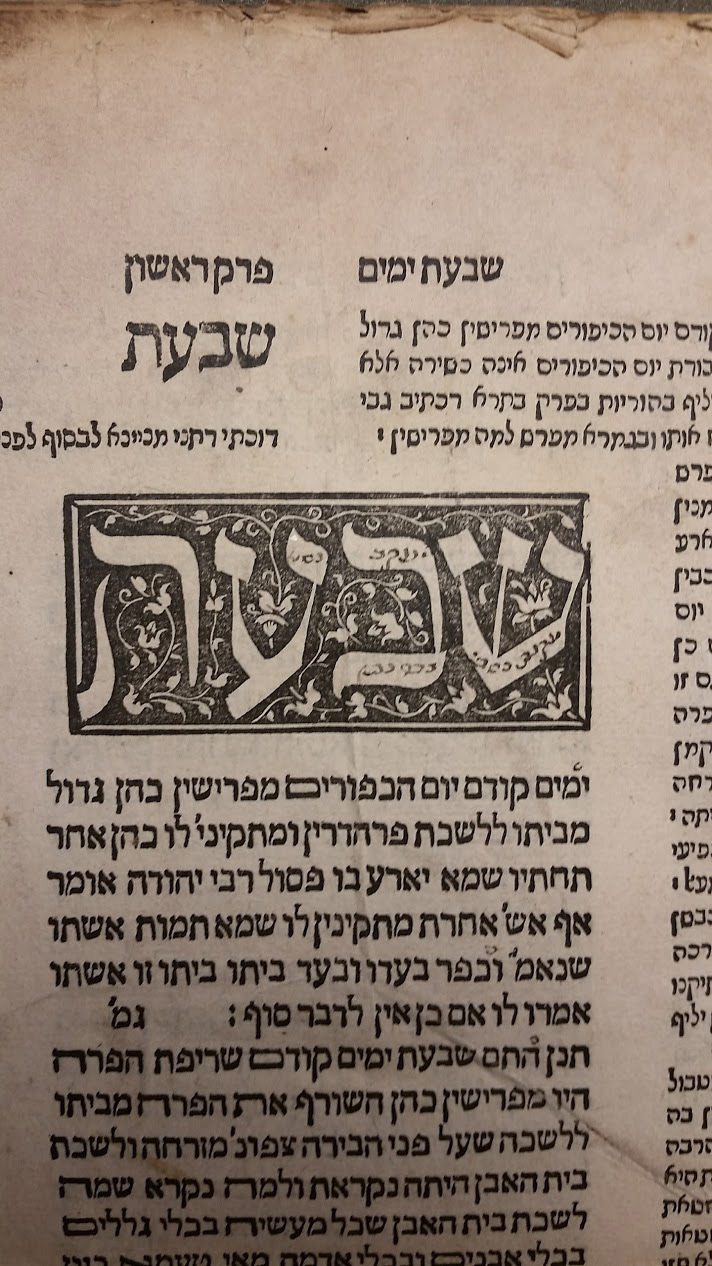 close up of ornately calligraphied hebrew word from the book in a black square with latticed ivy across it