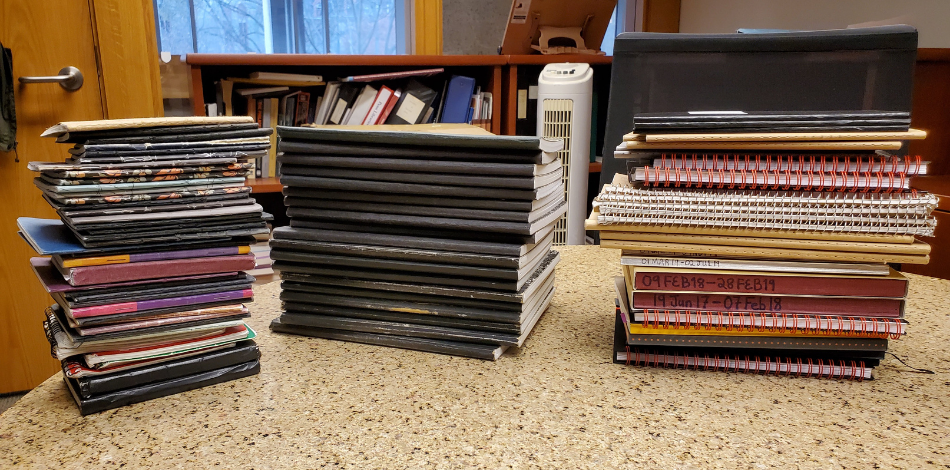 Three large stacks of bound notebooks sitting on a formica table.