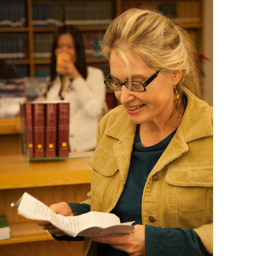Blonde woman stands in a library smiling down at a document