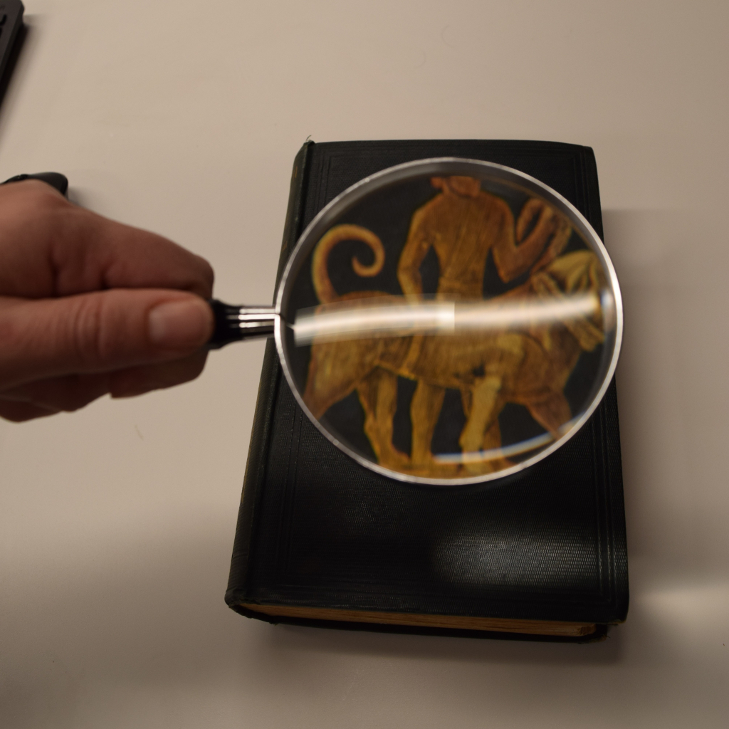 Magnifying glass enhances book cover showing image of a figure riding a large animal