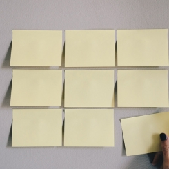 Grid of sticky notes on wall; Photo by Kelly Sikkema on Unsplash