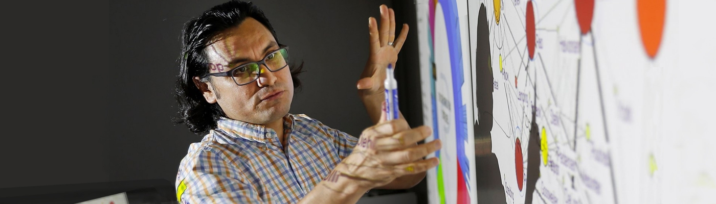 Manuel de la Cruz Gutierrez explaining a diagram on a whiteboard.