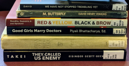 A stack of the following books: They Called Us Enemy; Still Life With Rice; Good Girls Marry Doctors; Red, Yellow, Black, and Brown; M. Butterfly; We Have Not Stopped Trembling Yet