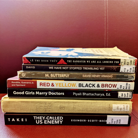 A stack of the following books: They Called Us Enemy; Still Life With Rice; Good Girls Marry Doctors; Red, Yellow, Black, and Brown; M. Butterfly; We Have Not Stopped Trembling Yet; The Gangster We Are All Looking For