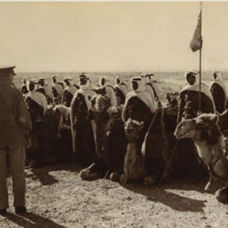 Black and white photo of men with camels