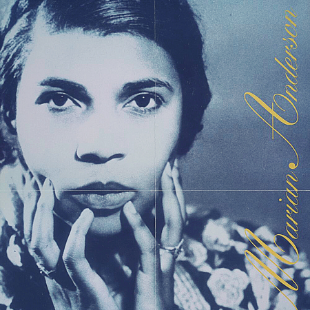 Black and white photo showing singer Marian Anderson in a close-up of her face with her hands resting on her cheeks.