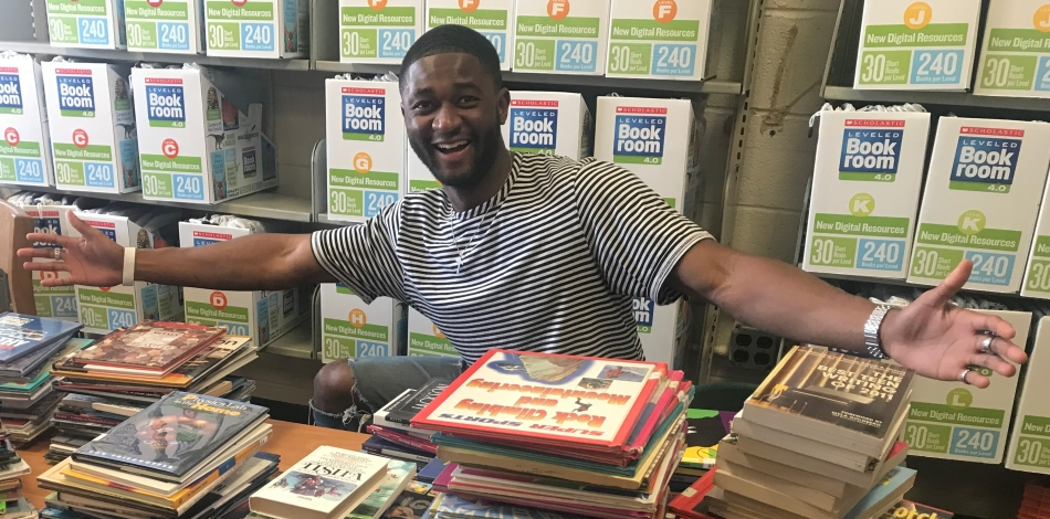 Photo of student worker with books on table