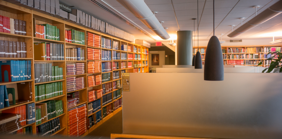 Photo looking down a line of desks with a bookshelf on the left-hand wall, filled with colorful books.