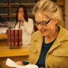 A woman stands in a library, smiling down at a document.