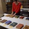 Two people review a display of rare books on a table